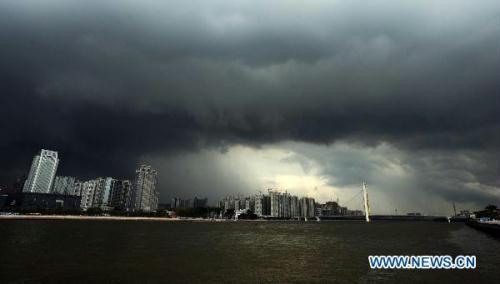 Dark clouds hang heavily over Guangzhou City, south China's Guangdong Province, July 21, 2010. Chanthu, the third tropical storm of the year, which strengthened early Wednesday is forecasted to land on south China's Hainan and Guangdong Province on July 22. (Xinhua/Liu Dawei)