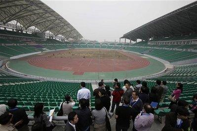 Journalists tour the University Town Main Stadium for the 2010 Asian Games, in Guangzhou, in south China's Guangdong province Monday, Dec. 14, 2009. The stadium will host Rugby and Soccer competition at the 16th Asian Games, which will be held in Guangzhou November 12-27, 2010.(AP Photo/Greg Baker)