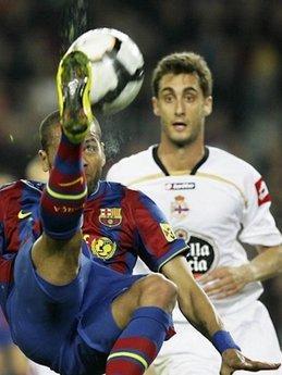 Battlefortheball:Barcelona'sBraziliandefenderDanielAlves(L)fightfortheballwithDeportivo'sdefenderAdrianLopez(R)duringaSpanishLeaguefootballmatchattheCampNouStadiuminBarcelona.Barcawon3-0.(AFP/JosepLago)