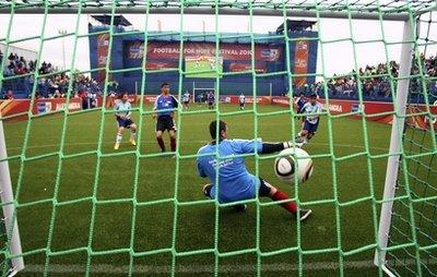 A goalkeeper for team Germany fails to save a goal during the Football for Hope Festival 2010 match against Argentina at Alexander township in Johannesburg, South Africa, Sunday July 4, 2010. 32 teams of young people from disadvantaged communities around the world come together in Johannesburg for a festival of education and culture that will culminate in a football tournament in a specially-constructed stadium in the community of Alexandra from July 4 to 10.(AP Photo/Themba Hadebe)