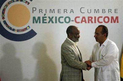 Haiti's President Rene Preval, left, shakes hands with Mexico's President Felipe Calderon during the opening ceremony of a meeting of leaders in a hotel in the outskirts of Playa del Carmen, Mexico, Sunday, Feb. 21, 2010. (AP Photo/ Eduardo Verdugo)