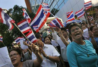 Pro-government protesters hold national flags as they gather near anti-government protesters to show their support to Prime Minister Abhisit Vejjajiva in Bangkok, Thailand Wednesday, April 21, 2010. (AP Photo/Vincent Yu)