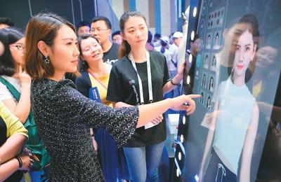 在2018中国国际大数据产业博览会上,参观者通过阿里巴巴的虚拟试衣镜体验现场试衣。新华社记者 欧东衢摄