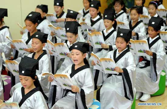 """Pupils wearing Hanfu, as ancient students did, recite Lunyu (or """"Analects"""" of Confucius) during a ceremony marking the 2565th birth anniversary of ancient Chinese philosopher Confucius in the Xiyou primary school in Hefei, capital of east China"""