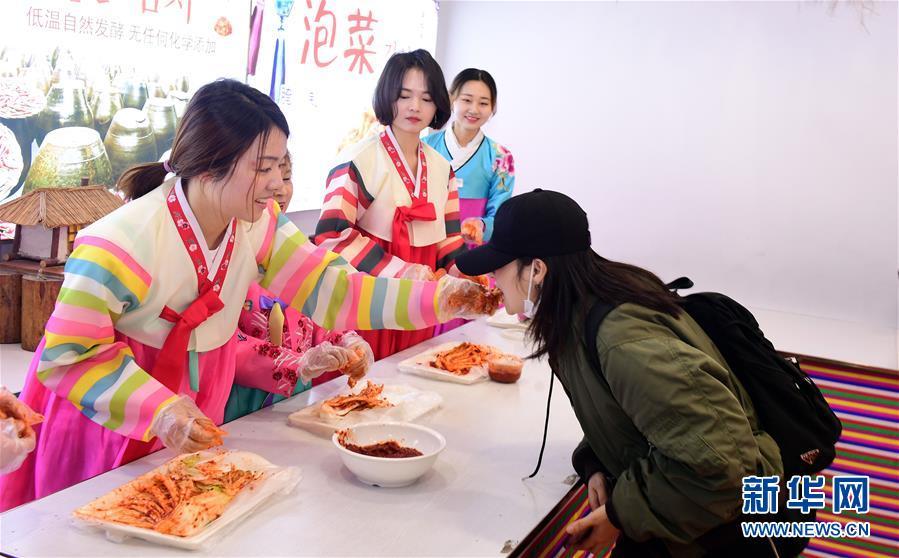 在红旗村民俗体验馆中,游客品尝辣白菜(4月16日摄)。新华社记者 林宏 摄