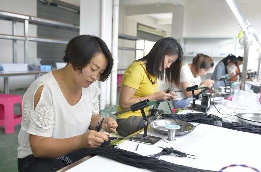 图为富源县富村镇搬迁群众在扶贫工厂务工创收