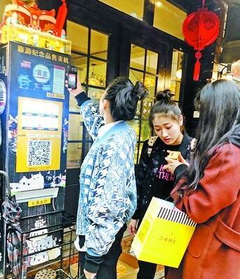 来厦游客用手机扫码购买旅游纪念品。