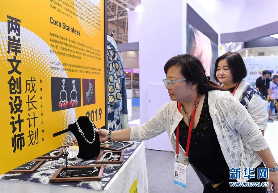 5月18日,台湾文创设计师林静瑜(前)在第二十一届海峡两岸经贸交易会上介绍她设计的饰品。 新华社记者 林善传 摄
