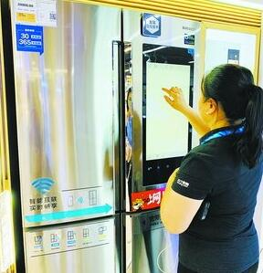 导购员在智能冰箱的电子屏幕上绘画,展示智能冰箱的种种功能。