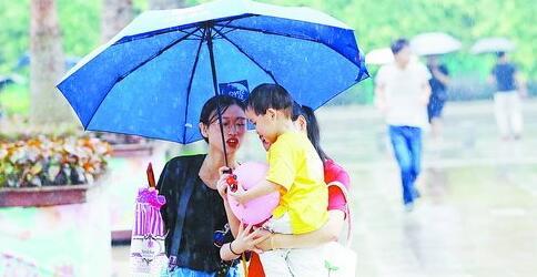傍晚突降阵雨,并未影响孩子过节的好心情。(本报记者 张奇辉 摄)
