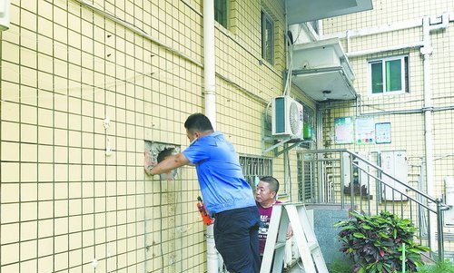 技术人员在对墙上的孔洞处进行检测