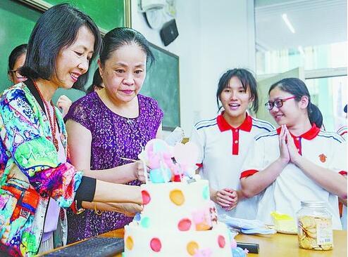 最后一堂班会课上,老师为五六月份过生日的同学切蛋糕。