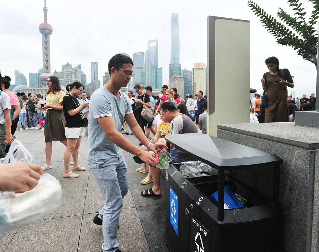 A man throws recyclables into a bin at the Bund, a riverside scenic spot in Shanghai, on June 30, 2019. [Photo/VCG]