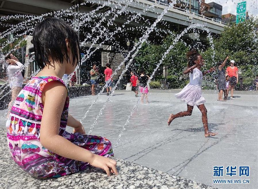 7月20日,在美国华盛顿,儿童在喷泉水池戏水降温。 新华社记者 刘杰 摄
