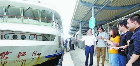 城迹70年。杨显东船长(左一白衣服)在厦鼓客运码头跟本报记者讲述码头的变化。