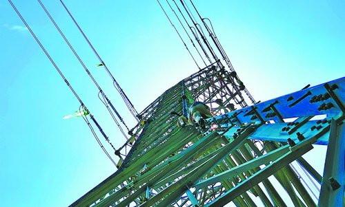 供电公司带电作业班电力人员在同安区滨海西大道的220千伏铁塔上进行高空作业。 (陈国信 摄)