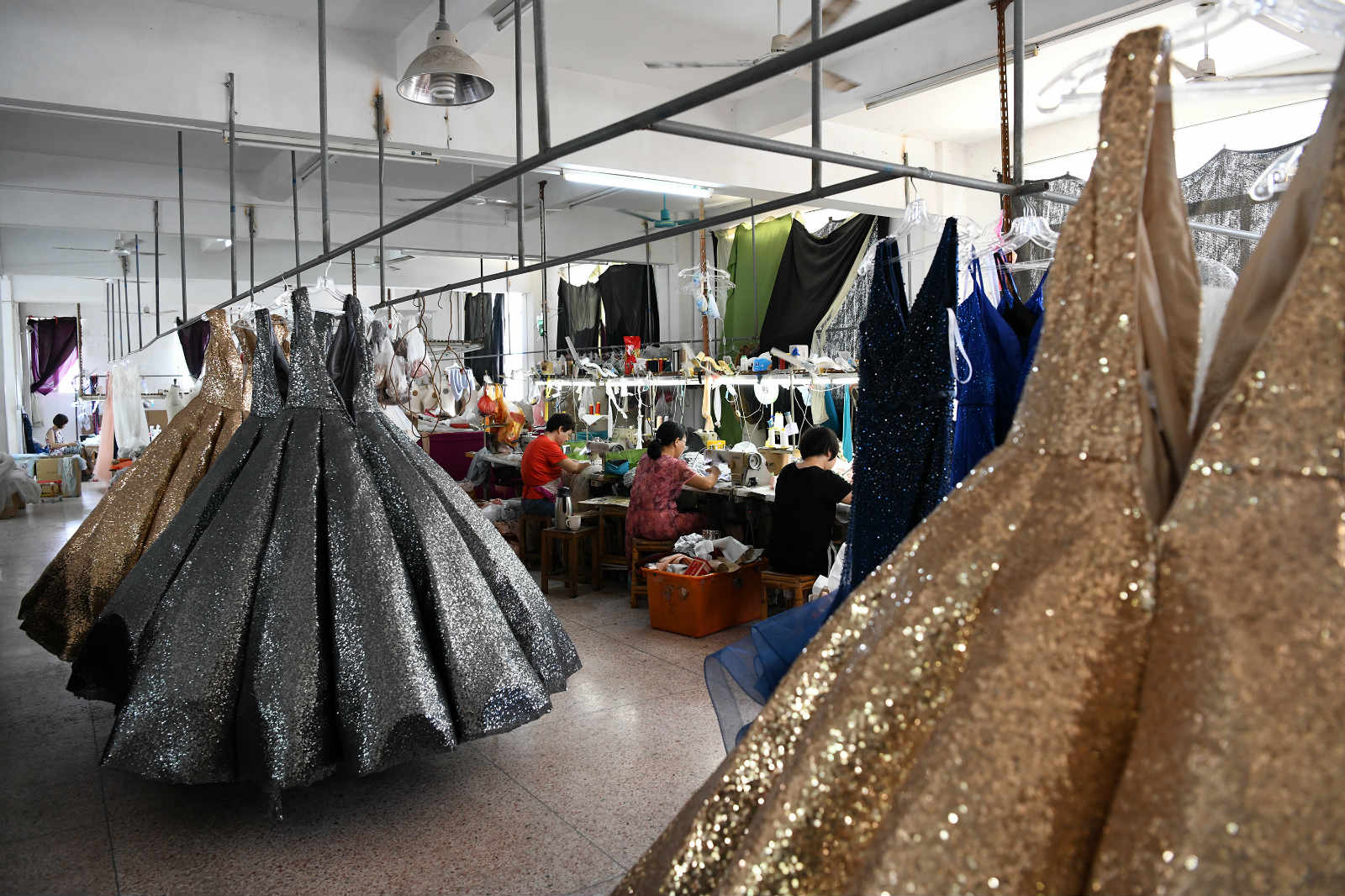 Embroiderers make dresses at a factory in Chaozhou, south China
