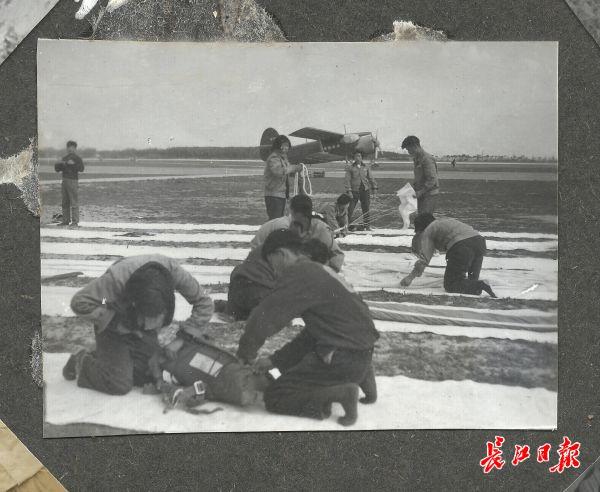 """湖北飞机跳伞运动代表队。升空跳伞的绝对安全要求运动员做到""""严如包公,心细如发""""。1959年,运动员在武昌南湖机场检查装备,折叠伞衣、伞绳,进行严格的叠伞训练"""