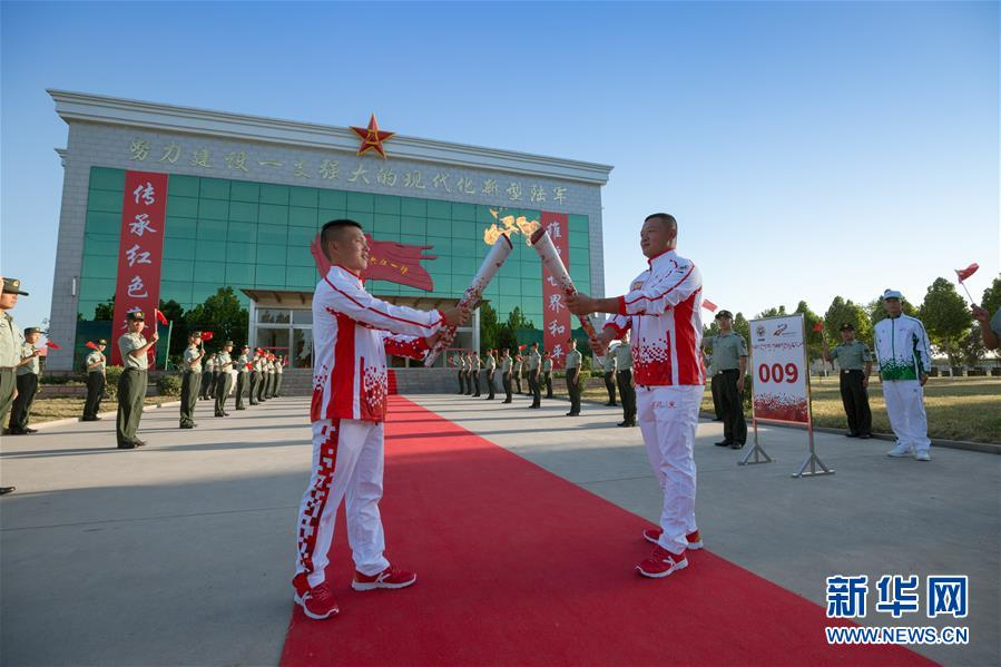 9月23日,火炬手王大毛(前左)与火炬手李旭(前右)在火炬传递活动中交接。新华社发(夏先杰 摄)