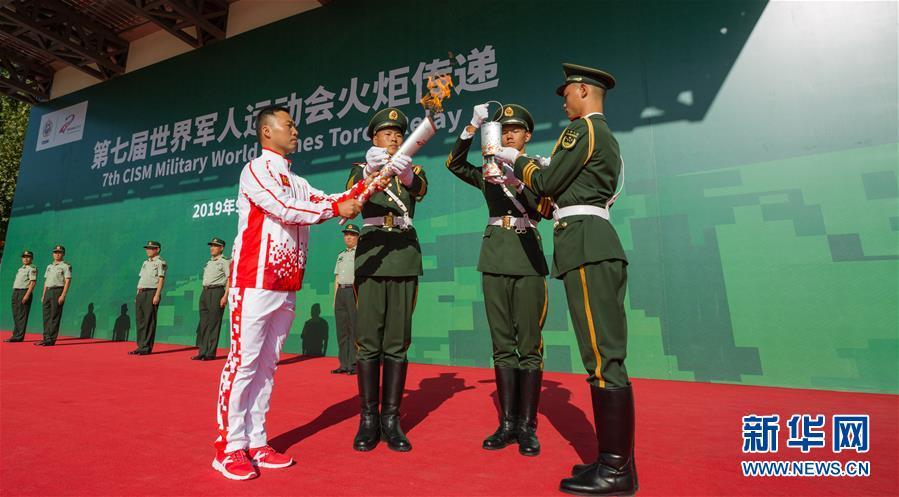 9月23日,最后一名火炬手张勇(前左一)在火炬传递活动中引回圣火火种。新华社发(王昆 摄)