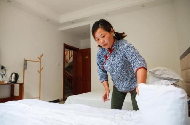 肖细雨在自己一手创办的农家乐为游客整理房间。张俊摄