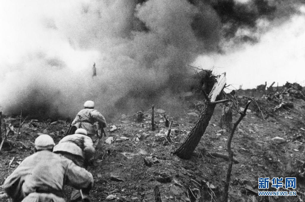 1952年,在上甘岭战役中,中国人民志愿军指战员在炮火支援下,攻上537.7高地北山。新华社发